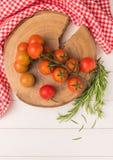 Tomates de cereja orgânicos com alecrins na tabela de madeira rústica Fotografia de Stock Royalty Free