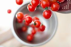 Tomates de cereja que caem do Colander do metal Imagens de Stock Royalty Free