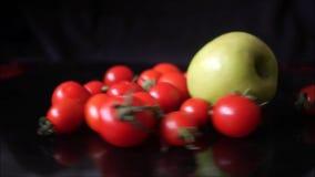 Tomates de cereja vermelhos e maçã verde que giram rapidamente no fundo preto video estoque