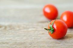 Tomates de cereja vermelhos frescos na tabela de madeira Fotos de Stock