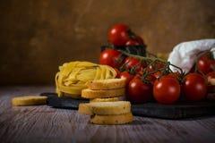 Tomates de cereja vermelhos na tabela de madeira do vintage com tagliatelle e bruschetta Imagens de Stock
