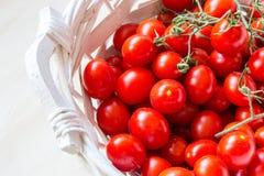 Tomates de cereja vermelhos pequenos em uma cesta de vime em uma tabela de madeira velha Foto de Stock