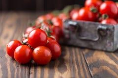 Tomates de cereja vermelhos pequenos no fundo rústico Tomates de cereja na videira Fotos de Stock