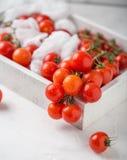 Tomates de cereja vermelhos pequenos no fundo rústico Tomates de cereja na videira Foto de Stock