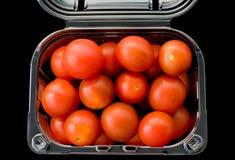 Tomates de cereza aislados en fondo negro Fotografía de archivo