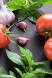 Tomates de cereza, albahaca fresca, ajo, en fondo de madera Fotografía de archivo
