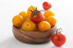 tomates de cereza amarillos y rojos en cuenco de madera en una tabla blanca Fotografía de archivo