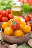 Tomates de cereza amarillos y rojos en los cuencos de madera, primer Imagen de archivo libre de regalías