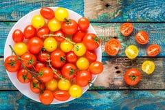 Tomates de cereza amarillos y rojos en un cuenco en la tabla de madera rústica Imagen de archivo libre de regalías