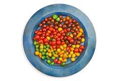 Tomates de cereza amarillos y verdes rojos coloridos en la bandeja azul redonda en un fondo blanco Aislado Fotografía de archivo libre de regalías