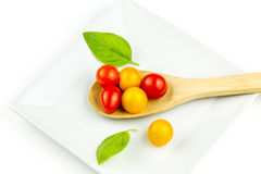 Tomates de cereza coloridos en la cuchara de madera Foto de archivo libre de regalías