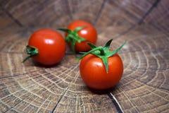 Tomates de cereza con la manija verde en la tabla de madera Fotos de archivo libres de regalías