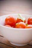 Tomates de cereza con perejil en un cuenco blanco Imagenes de archivo