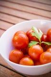 Tomates de cereza con perejil en un cuenco blanco Fotografía de archivo