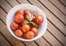 Tomates de cereza con perejil en un cuenco blanco Imagen de archivo libre de regalías