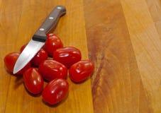 Tomates de cereza con un cuchillo Fotografía de archivo libre de regalías