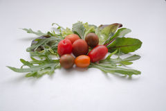 Tomates de cereza con verdes frondosos Imágenes de archivo libres de regalías