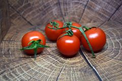 Tomates de cereza deliciosos en una placa de madera Fotografía de archivo libre de regalías