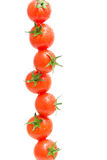 Tomates de cereza en descensos del agua en un fondo blanco Fotografía de archivo