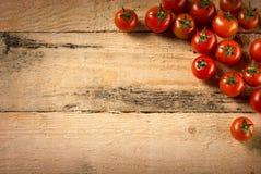 Tomates de cereza en el fondo de madera Imagen de archivo