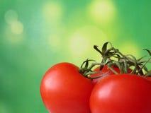 Tomates de cereza en fondo verde blured imagen de archivo