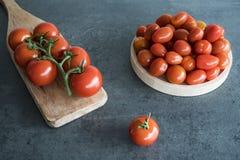 Tomates de cereza en la placa y la tabla de cortar de madera, foto de archivo