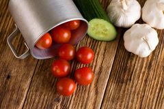 Tomates de cereza en la taza de aluminio y la diversa verdura Fotografía de archivo libre de regalías