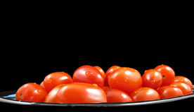 Tomates de cereza en negro Fotos de archivo libres de regalías