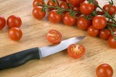 Tomates de cereza en tajadera Fotos de archivo