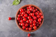 Tomates de cereza en un cuenco de la arcilla Fondo colorido de los tomates de los tomates Fotografía de archivo