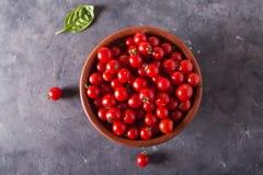 Tomates de cereza en un cuenco de la arcilla Fondo colorido de los tomates de los tomates Imagen de archivo