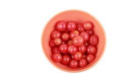 Tomates de cereza en un tazón de fuente anaranjado Imágenes de archivo libres de regalías