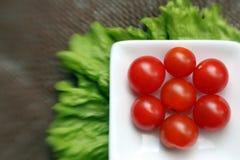 Tomates de cereza en un tazón de fuente blanco cuadrado Fotografía de archivo