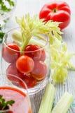 Tomates de cereza en un vidrio con apio en una tabla de madera Imagenes de archivo
