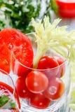 Tomates de cereza en un vidrio con apio en una tabla de madera Imagen de archivo