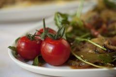 Tomates de cereza en una placa Imagenes de archivo