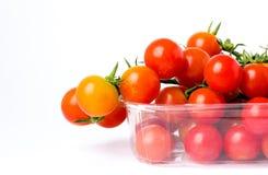 Tomates de cereza en una rama en caja plástica al por menor transparente Imagen de archivo libre de regalías