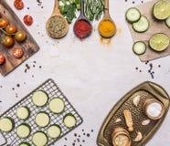 Tomates de cereza en una tabla de cortar, tres clases de condimento en cucharas de madera, calabacín cortado la rejilla para asar Foto de archivo