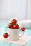 Tomates de cereza en una taza Imagenes de archivo