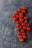 Tomates de cereza en vid contra superficie de piedra negra Fotografía de archivo libre de regalías