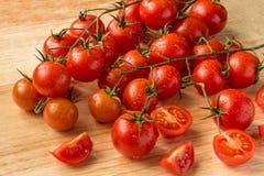 Tomates de cereza - fondo de madera de los descensos del agua Imagen de archivo