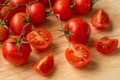 Tomates de cereza - fondo de madera de los descensos del agua Imagen de archivo libre de regalías