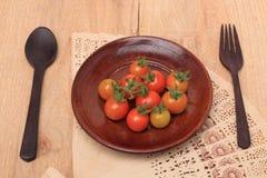 Tomates de cereza frescos en la madera de la placa Imagen de archivo libre de regalías