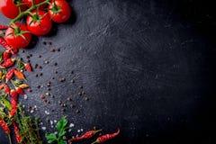 Tomates de cereza frescos en un fondo negro con las especias con la placa de la pizarra Visión superior con el espacio de la copi Imagen de archivo