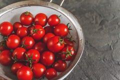 tomates de cereza lavados enteros crudos en un colador en un concret oscuro fotografía de archivo libre de regalías