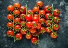Tomates de cereza orgánicos frescos en la tabla negra fotografía de archivo libre de regalías