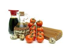 Tomates de cereza, pastas, huevos de codornices, aceite de oliva y salsa de soja en w Imagen de archivo