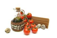 Tomates de cereza, pastas, huevos de codornices y aceite de oliva en una parte posterior del blanco Foto de archivo