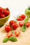Tomates de cereza rebanados con albahaca Fotos de archivo libres de regalías