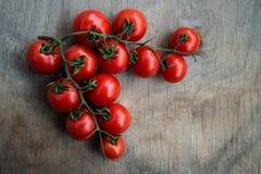 Tomates de cereza red delicious frescos en un tablero de la mesa de madera viejo b Fotografía de archivo libre de regalías